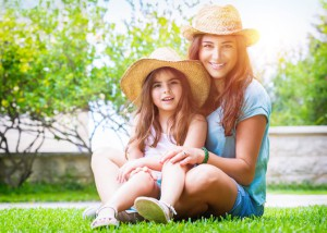 Happy family in the garden, beautiful mother with her little cute daughter sitting on fresh green grass on a backyard, with pleasure spending time together