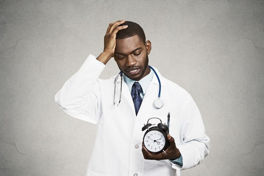 Closeup portrait overwhelmed with busy schedule health care professional doctor, nurse, dentist with stethoscope holding alarm clock running out of time having headache isolated black grey background